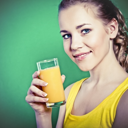 Beautiful girl drinks natural orange juice photo