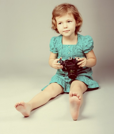 Portrait of baby girl holding photo camera photo