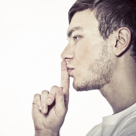 Young man with his finger over his mouth Stock Photo - 13117179