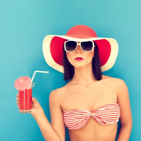 beach breast: sensual woman with sunglasses drinking a cocktail