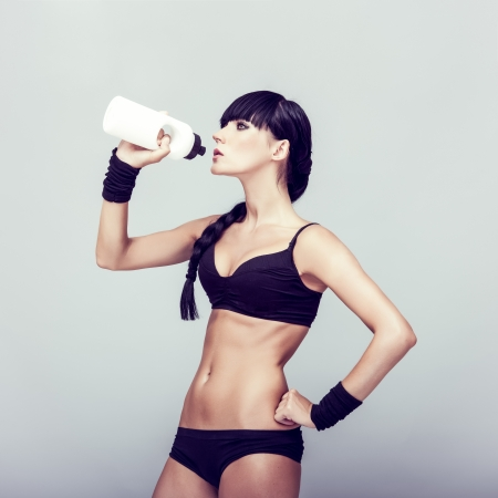sporty muscular woman drinking water photo