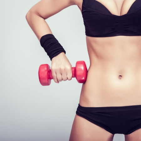 athletic body with dumbbells close-up photo