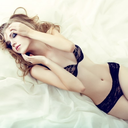 nude blond: sensual girl sleeping in white bed Stock Photo