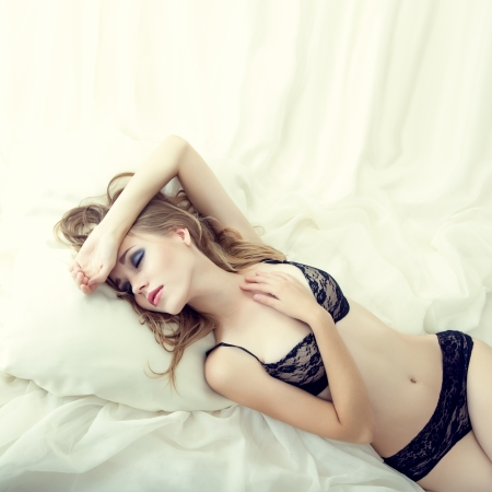 nude female body model: Fashion portrait of a sensual girl sleeping in white bed