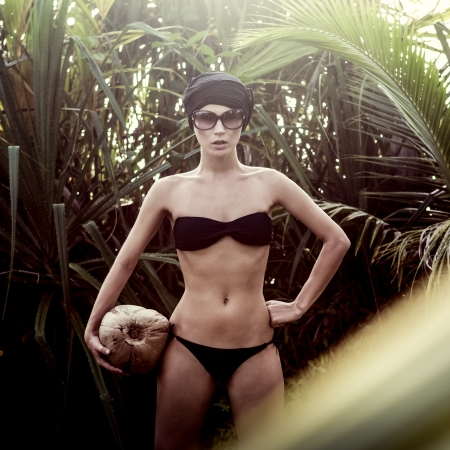 girl in a tropical jungle with coconut photo