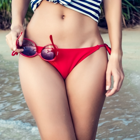 tanned body: Closeup of a female body in a swimsuit with sunglasses