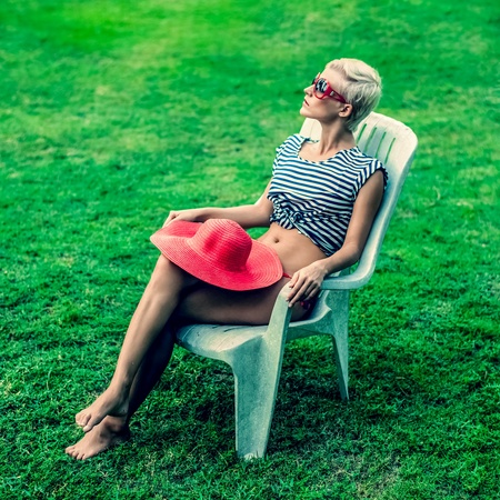 fashion girl sitting resting on a chair in the park Stock Photo