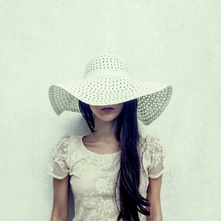 elegance fashion girls look sensuality young: fashion portrait of a sensual girl in a hat against the wall Stock Photo