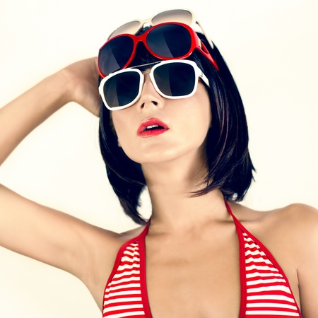 Portrait of a girl in a fashionable swimsuit and sunglasses photo