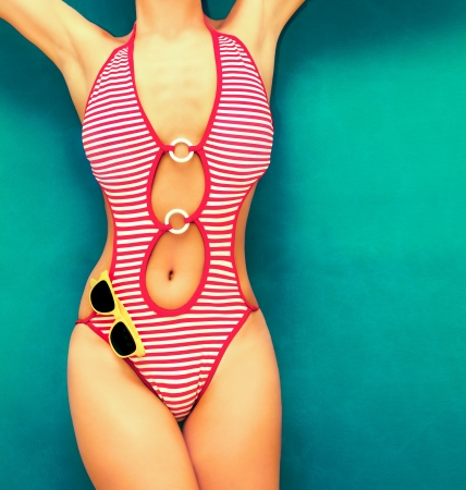 torso of a girl in a fashionable black bathing suit on a bright background photo