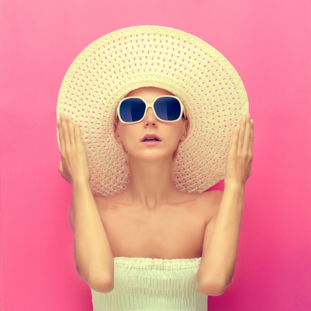 summer clothing: portrait of a girl in a hat on a pink  background