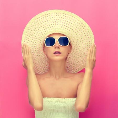 modelos negras: retrato de una niña en un sombrero sobre un fondo de color rosa