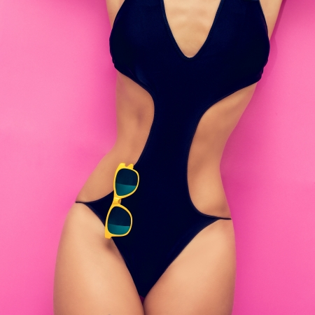 torso of a girl in a fashionable black bathing suit on a bright background