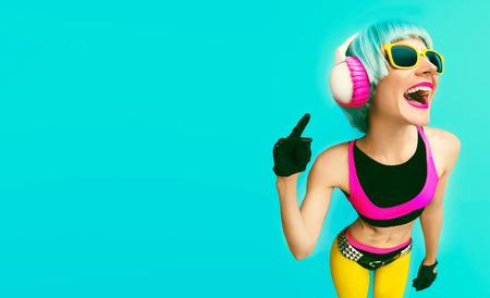 音楽を聴く、青の背景に明るい服で華やかなファッション dj の女の子。 写真素材
