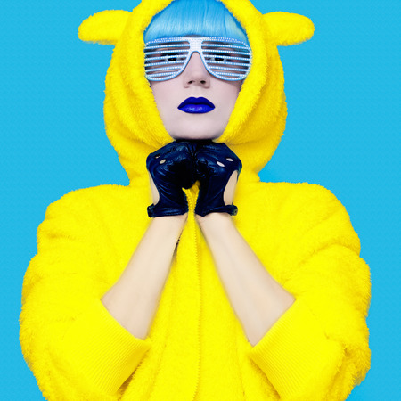 Teddy bear crazy girl in a bright hoodie on a blue background color exclusive photo