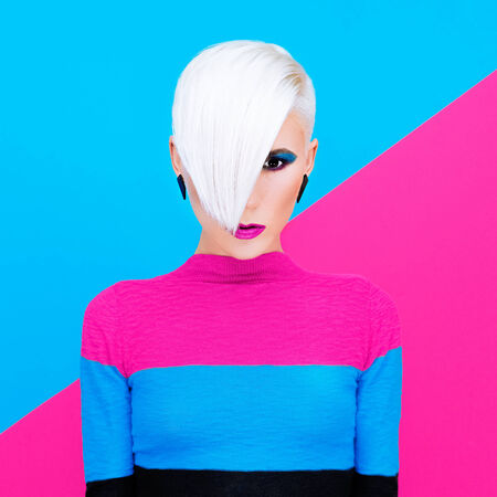 Fashion blond model with trendy hairstyle on a colorful background. Art photo photo