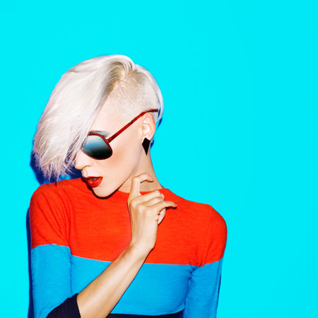 red and blue: fashion blond woman with trendy hairstyle and sunglasses on a blue background
