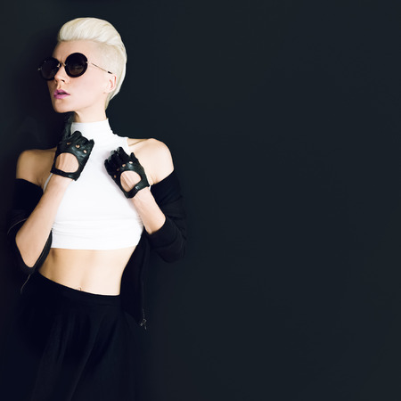 glamor model on black background in trendy gloves and sunglasses fall fashion style Stock Photo