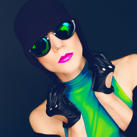 bright glamorous lady on black background in trendy sunglasses and hat autumn fashion style