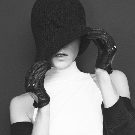 girl shadow: glamor model on black background in trendy gloves and hat autumn fashion style