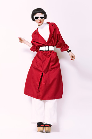 portrait fashion model in red coat on a white background