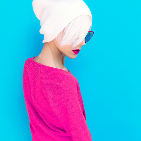 red and blue: fashion blond model with trendy cap and sunglasses on a blue background Stock Photo