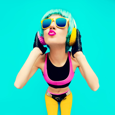 Glamorous Fashion DJ Girl in bright clothes on a blue background listening to Music.