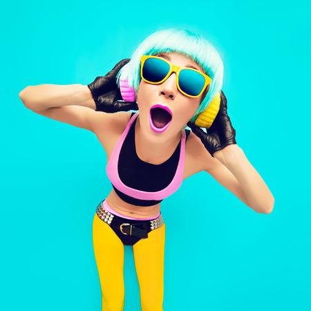 Glamoureuze party DJ Meisje in heldere kleren op een blauwe achtergrond luisteren naar muziek.