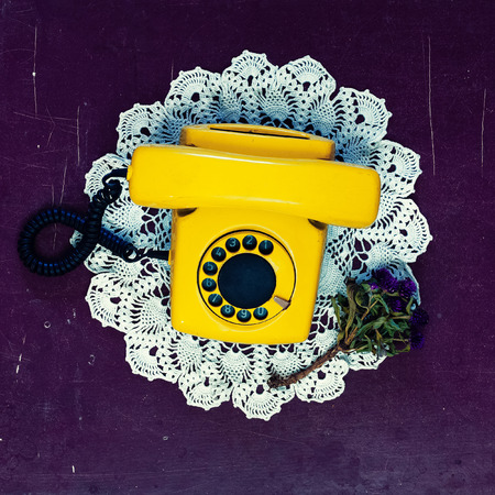 dialing: Yellow vintage telephone old wooden background