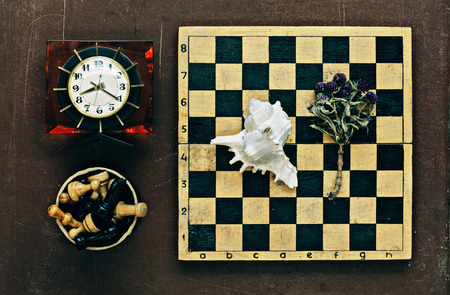 Chess, clock and seashell on old wooden background photo