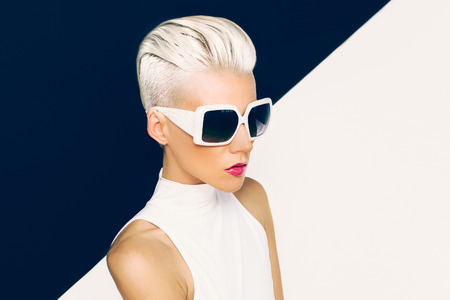 glasses model: Blonde model in trendy sunglasses with stylish Haircut. Fashion photo Stock Photo