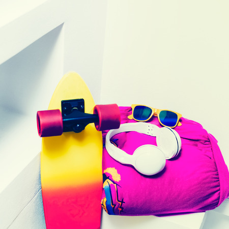 Extreme sports accessories. Skateboard and bright fashionable clothes. photo