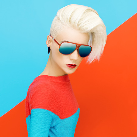 blonde lady with fashionable hairstyle and sanglasses on bright background. fashion photo