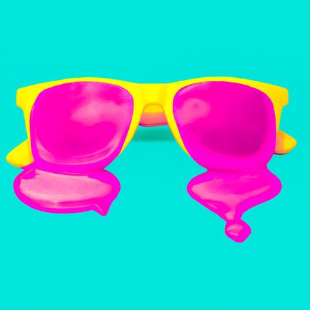파란색 배경에 독점 노란색 hipster 선글라스입니다. 핑크 페인트가 떨어지는. 폭발 여름 색상