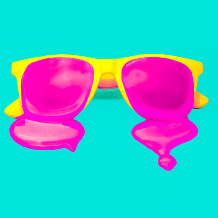 explosion: Exclusive yellow hipster sunglasses on blue background. dripping pink paint. explosion summer colors Stock Photo