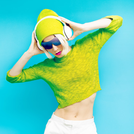 Glamorous Lada DJ in fashionable sportswear listening to Musik on blue background