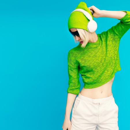 파란색 배경에 음악원을 듣고 밝은 옷 매력적인 라다의 DJ