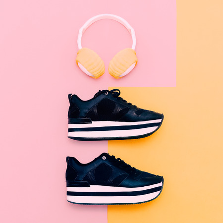 urban style: Trendy white headphones and sneakers on vanilla background. Urban summer time