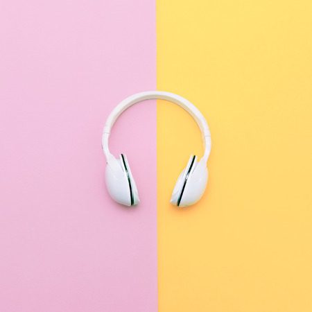 Fashion white headphones on vanilla background. Urban summer time