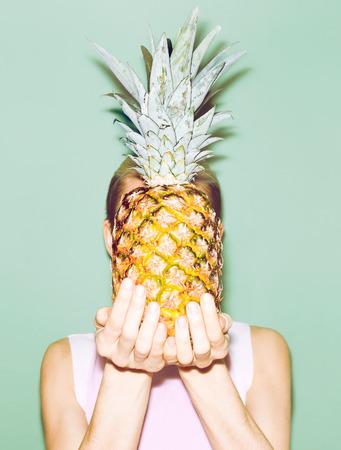 fashion: girl holding pineapple. Fashionable stylish summer