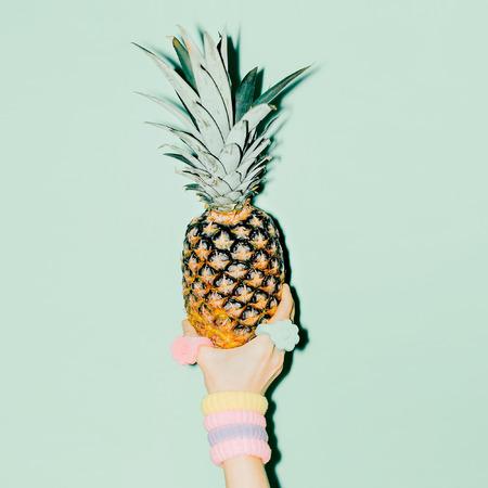 Fashion photo. Hand holding pineapple. vanilla style