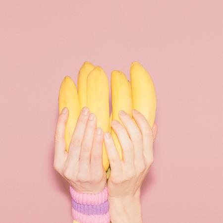 バナナの束を保持する手。ファッション、バニラ スタイル ミニマリズム