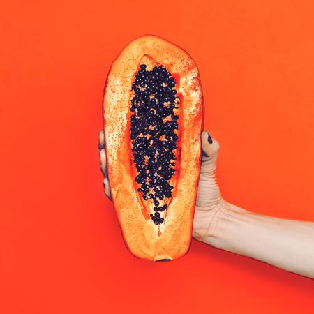 패션 사진. 파파야 열매와 팔. 추세에 오렌지 컬러