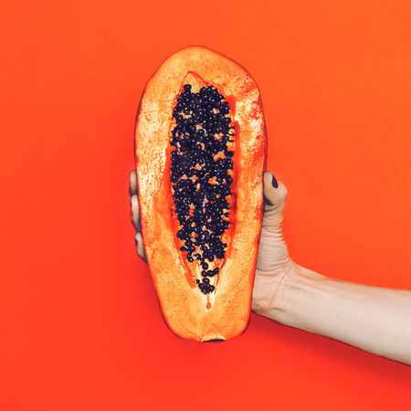 Fashion photo. arm with papaya fruit. orange color in the trend Banque d'images