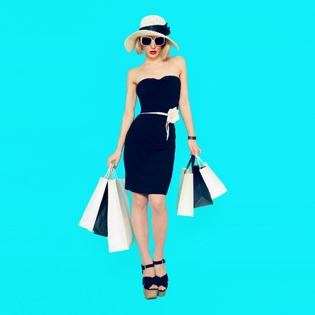 青の背景に買い物袋を持つスタイリッシュなショッピング女性 写真素材