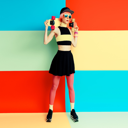Glamour model holding skateboard on bright exclusive background, hipster style Archivio Fotografico