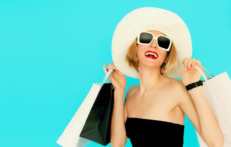 青の背景に袋を保持している幸せなショッピング女性