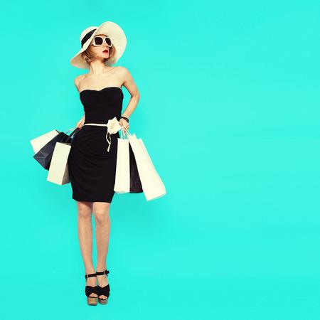쇼핑 스타일. 파란색 배경에 매력적인 여자 가방을 들고 스톡 콘텐츠