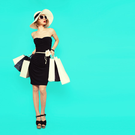 Shopping style. Glamorous lady holding bags on blue background