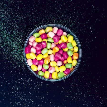 advantaged: Bucket Sweet Drops on black background shining. Minimalist fashion